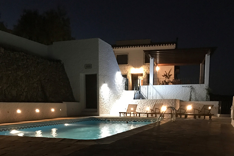 The pool and jacuzzi lit up by night